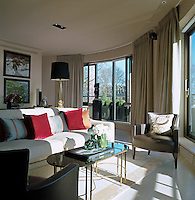 The semi-circular contemporary sitting room is surrounded by windows which fill the room with light