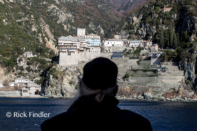 Mount Athos - The Holy Mountain.<br /> A monk looks toward Dionysiou from the ferry boat. Dionysiou, which was built in the 14th century, is one of twenty monasteries that are on the peninsula. <br /> <br /> Photographer: Rick Findler