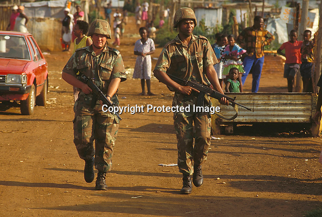 PSMILIT27015.Defence Force. Military.  Two former enemies in the new SADF. Two men walking in the dirtstreet with guns. Weapons. Squatter camps, poverty, people on the street, unemployement..©Per - Anders Pettersson /iAfrika photos