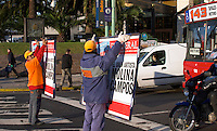 A pedestrian crossing on a street, three persons carrying publicity boards that are held up and shown to the drivers in the cars, a kind of manual movable advertising on the street. Pedestrians walking, a bus stopped at a red light. Buenos Aires Argentina, South America