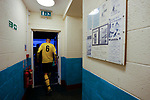 Hebburn's Jack Donaghy emerges for the second half, next to a selection of framed Penrith programmes. Penrith AFC V Hebburn Town, Northern League Division One, 22nd December 2018. Penrith are the only Cumbrian team in the Northern League. All the other teams are based across the Pennines in the north east.<br />