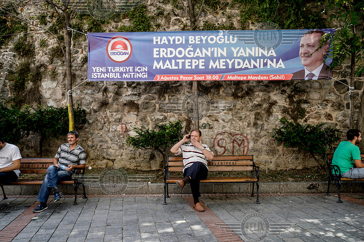 A man sitting on a park bench beneath the Galata Tower smokes a cigarette while making a mobile phone call. A banner behind him a banner advertises a political rally.