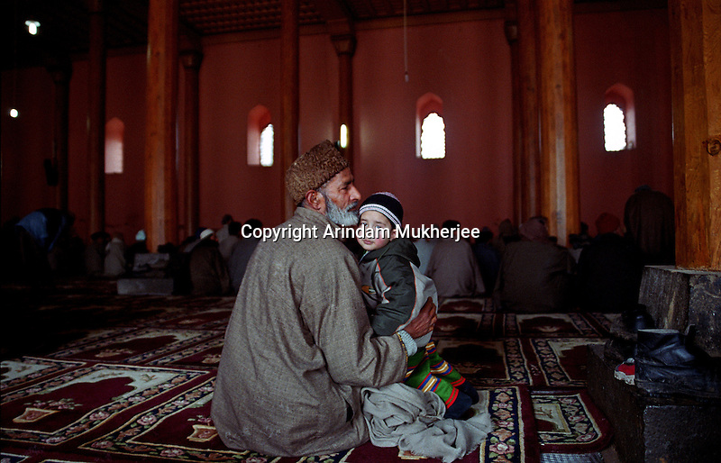 A Kashmiri Muslim with his grandson at world famous Jamia Mosque at Srinagar, Kashmir Valley, India