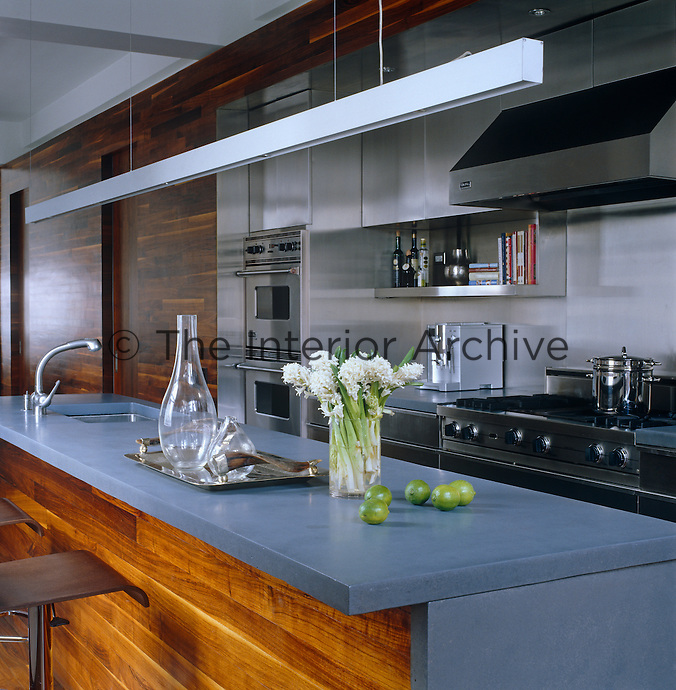 The cast concrete and American walnut kitchen island also functions as a breakfast bar