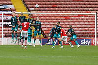 Bambo Diaby of Barnsley (L) takes a free kick over the Swansea wall during the Sky Bet Championship match between Barnsley and Swansea City at Oakwell Stadium, Barnsley, England, UK. Saturday 19 October 2019