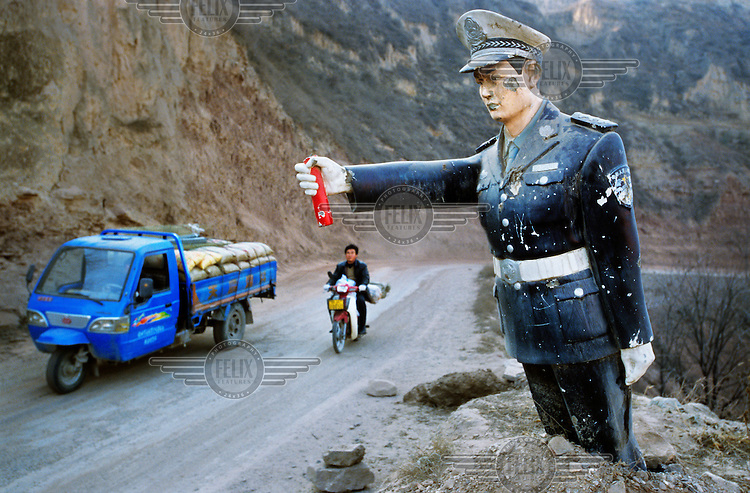 A truck and a motorcycle pass a damaged statue of a policeman which stands on the bend of a road in the Loess Plateau....