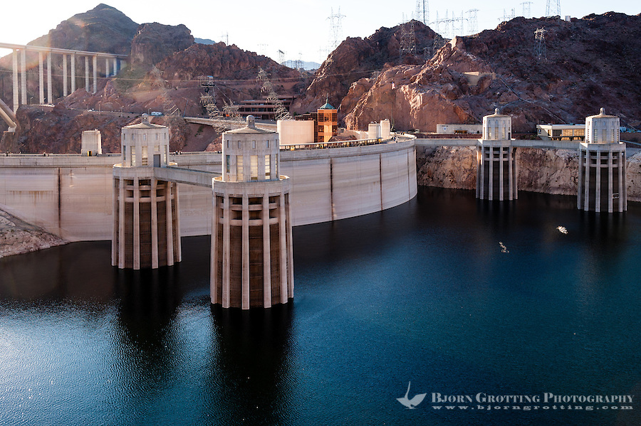 United States, Arizona. The Hoover Dam is a large concrete dam in the Black Canyon of the Colorado River. Cylindical intake towers in front of the dam structure.