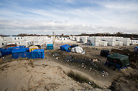 """The containers' """"new camp"""" protected by high fences, security guards and finger prints reader at the gate used as the """"key"""" to enter.<br /> <br /> Calais Jungle Camp.<br /> <br /> Under the Sky of Calais & Dunkirk. Two Camps, Two Sides of the Same Coin: Not 'migrants', Not 'refugees', just Humans.<br /> <br /> France, 24-30/03/2016. Documenting (and following) Zekra and her experience in the two French camps at the gate of the United Kingdom: Calais' """"Jungle"""" and Dunkirk's """"Grande-Synthe"""". Zekra lives in London but she is originally from Basra in Iraq. Zekra and her family had to flee Kuwait - where they moved for working reason - due to the """"Gulf War"""", and to the Western Countries' will to """"export Democracy in Iraq"""". Zekra is a self-motivated volunteer and founder of """"Happy Ravers"""", a group of people (not a NGO or a charity) linked to each other because of their love for rave parties but also men and women who meet up every week to help homeless people and other people in need in Central London. (Here there are some of the stories I covered about Zekra and """"Happy Ravers"""": http://bit.ly/1XVj1Cg & http://bit.ly/24kcGQz & http://bit.ly/1TY0dPO). Zekra worked as an English teacher in the adult school at Dunkirk's """"Grande-Synthe"""" camp and as a cultural mediator and Arabic translator for two medic teams in Calais' """"Jungle"""". Please read her story at the beginning of this reportage."""