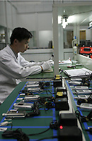 A lab technician works nearby more than a dozen handsets during their battery charge test at the Ninbo Bird factory in Fenghua, China. The stiff competition from both domestic and foreign brands in an already-saturated Chinese market has prompted the company to start its own Research and Development centre and seek markets in countries like India..31-OCT-03