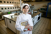 Student Pauline Meillier poses for the photographer holding Michel Maincent-Morel's book La Cuisine de Reference in a kitchen at the Ecole Superieure de Cuisine Francaise Gregoire Ferrandi cooking school in Paris, France, 18 December 2007.