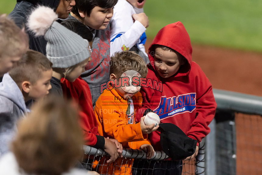 A young fan and his friends react after receiving a baseball from a player during a Pacific Coast League game between the Omaha Storm Chasers and the Memphis Redbirds on April 26, 2019 at Werner Park in Omaha, Nebraska. Memphis defeated Omaha 7-3. (Zachary Lucy/Four Seam Images)