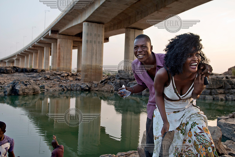 A man and a woman play about on the banks of the Niger River. In the background is a Chinese built bridge that was opened in September 2011 and is the third crossing of the Niger in Bamako.