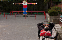 A homeless man rests on a bench in a park near Tsukiji Tokyo, Japan. Friday April 13th 2012