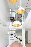 Pendant lights hang from a double height ceiling above a dining table and chairs. The spacious room has an open staircase with glass side panels.