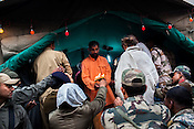Soldiers take blessings from a priest at a make shift temple in Chandanwari, the base camp of the journey in Kashmir, India. Hindu pilgrims brave sub zero temperature and high latitude passes and make their pilgrimage to reach the sacred Amarnath cave, which houses a lingam - a stylized phallus, worshiped by Hindus as a symbol of God Shiva. Photo: Sanjit Das/Panos