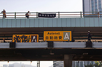 """A black banner read """"Shame on inline with police"""" is seen hanged above Cross-Harbour Tunnel.<br /> Siege at Polytechnic University.<br /> Police surround the university campus after pro-democratic protesters blocked the cross-harbour tunnel and the major road outside the campus.<br /> Hong Kong protest continuous on its sixth months. A citywide strike called for started on Monday 11 November, 2019 which brought parts of Hong Kong to halt as MTR stations closed and multiple roadblocks were erected. Hong Kong, 17.11.2019"""