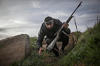 In this Saturday, Dec. 15, 2012 photo, a Syrian rebel fighter takes cover during heavy clashes inside one militar academy besieged by rebels at the north of Aleppo, Syria. The Free Syrian Army took control over the Academy after several hours battling the troops loyal to President Bashar al-Assad. Among the casualities are one FSA General and one Syrian journalist. (AP Photo/Narciso Contreras)