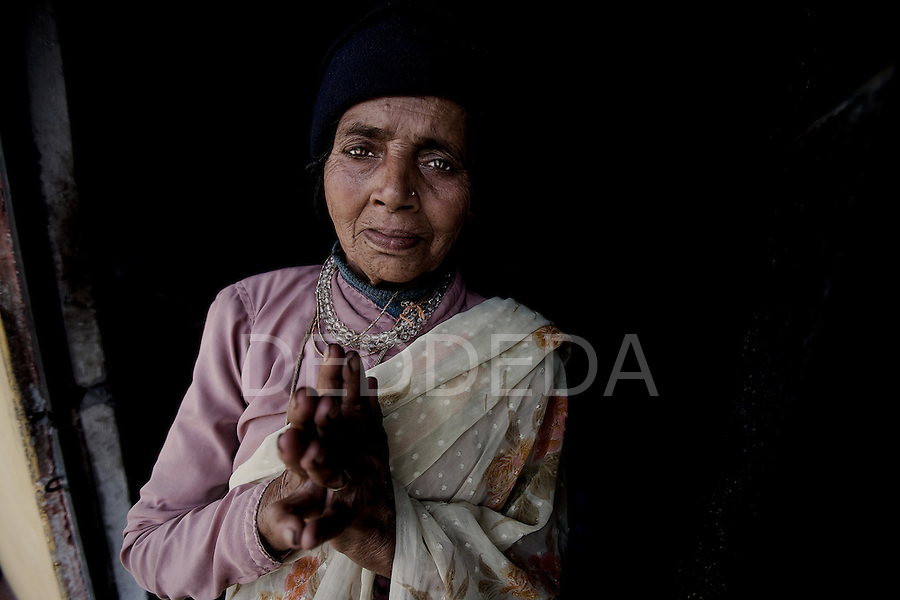 """An elderly woman greets with a """"Namaste"""" at an """"Aged Shelter"""" in Pokhara, Nepal. The shelter is a place for seniors to live who have no other family members to look after them. The shelter has no running water, the cooking is done over a fire, there are no nurses or doctors, no heating, and no medication available for the residents."""