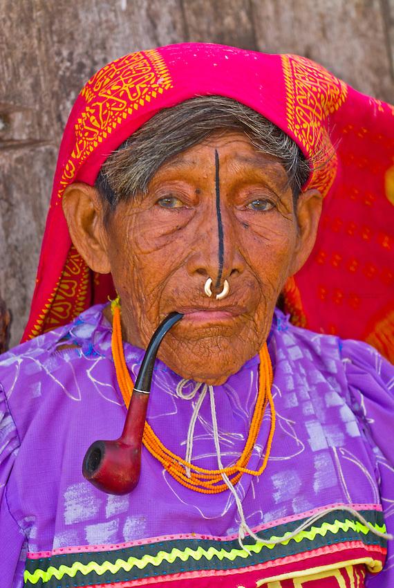 Kuna Indian woman with nosering smoking a pipe (wearing native costume with Mola embroderies), Corbisky Island, San Blas Islands (Kuna Yala), Caribbean Sea, Panama