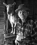 "December 1971:  Modesto, California—Dad Walkling—Dad greets the new year with Goat milk from Brigette.  I first met Orlando ""Dad"" Walkling at his house in the airport district of Modesto just before his 104th birthday.  Walkling was born in Indian Territory January 2, 1868, near a town now called McAlester, Oklahoma.  His mother was Shawnee and his father, whom he didn't remember, was an Englishman named Orlando.  He later used the name Walkling instead of his Indian name of Skipocase.  On September 16, 1893, Skipocase O. Walkling, then 25 years old, was among thousands of settlers who rode into the Cherokee Strip Land Run of Oklahoma to make a free land claim.  Walkling told of how he rode into the 226-mile long ""Strip"" to claim 160 acres.  ""There were thousands of men who waited at the line until noon that day.  The army gun was fired and chaos broke out. Every man carried a gun. There was no law, no sheriff, nothing.  People had to fight for their claim even though they were first.""  Walkling made a claim, but later gave it up when he had a chance to farm a piece of land in Noble County, Oklahoma.  He cleared the land with six yoke of oxen and planted peach orchards.  He and his first wife ran a combination grocery store and hotel there.  He had nearly 1,000 trees and began a cannery to process the crops.  ""One day when the train came in a woman dressed like a Salvation Army woman handed me a bundle as I stood on the ramp, then she jumped back into the train.  I opened it and there was a pair of twins, a boy and a girl,"" Walkling said.  He and his wife did not have children, so they adopted the twins legally and raised them.  He said they raised six others but did not adopt them.  He came to Modesto in 1944 at 76 years of age and went to work for a meat firm before he opened a poultry store.  After that store closed, he made bullwhips and wove rope for truckers at his home.  In 1968, Dad Walking, then 100 years old, visited Oklahoma for the 75th anniver"