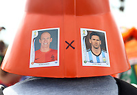 A Netherlands supporter wears a hat with panini stickers billing today's fixture as Arjen Robben of Netherlands vs Lionel Messi of Argentina