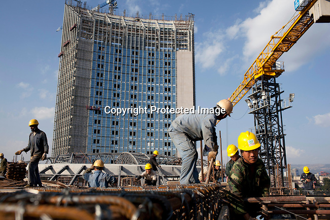 ADDIS ABABA, ETHIOPIA - NOVEMBER 17: Chinese construction workers build the new African Union Buildings on November 17, 2010 in Addis Ababa, Ethiopia. The building is built for free. Chinese companies are investing and working all over Africa and in Ethiopia they are mainly occupied with infrastructure projects around the country. Photo by: Per-Anders Pettersson