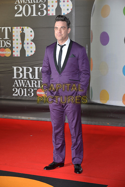 Robbie Williams.The Brit Awards 2013 arrivals at the O2, Greenwich, London, England 20th February 2013.The Brits full length purple suit black tie lapel white shirt hands in pockets .CAP/PL.©Phil Loftus/Capital Pictures.