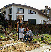 Caroline de Aragues, her husband Richard and their children stand in their garden with their new home in the background