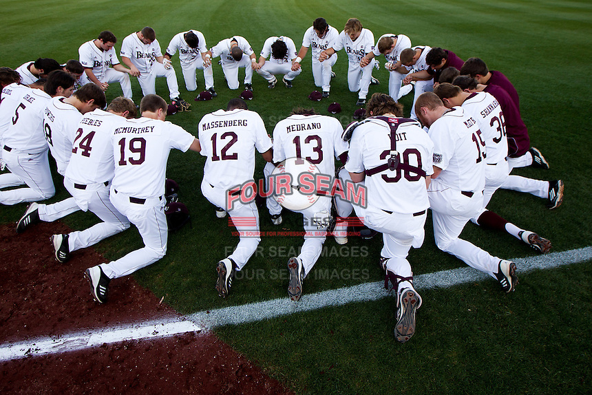 Members of the Missouri State Bears pray on the field prior to a game against the Purdue Boilermakers at Hammons Field on March 13, 2012 in Springfield, Missouri. (David Welker / Four Seam Images)