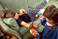 Sisters playing doctor and taking blood pressure on sofa age 3 and 5.  Western Springs  Illinois USA
