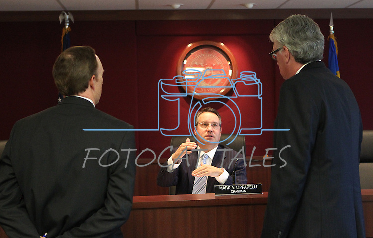 Gaming Control Board Chairman Mark Lipparelli, center, talks to Deputy Attorney General Michael Somps, left, and attorney Mark Clayton during a break in a meeting in Carson City, Nev., on Wednesday, Dec. 7, 2011. .Photo by Cathleen Allison