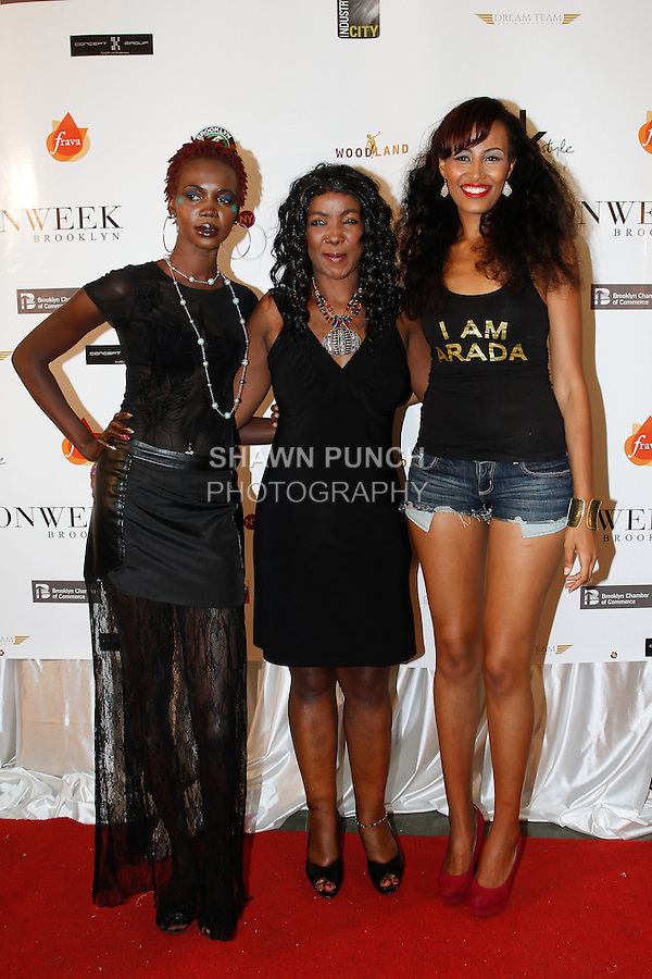 Guest poses on red carpet with models, after her Kemunto Fashions Spring Summer 2014 collection fashion show, during Fashion Week Brooklyn Spring Summer 2014, in Brooklyn, New York on October 5, 2013.