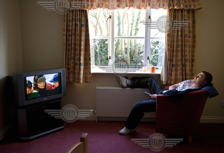 Sam Butler watches television in a care home in Peterborough. 25 year old Sam Butler was born with HIV as his mother was a heroin addict; he was also born addicted to the drug. Sam is now suffering from Aids-related brain degeneration.