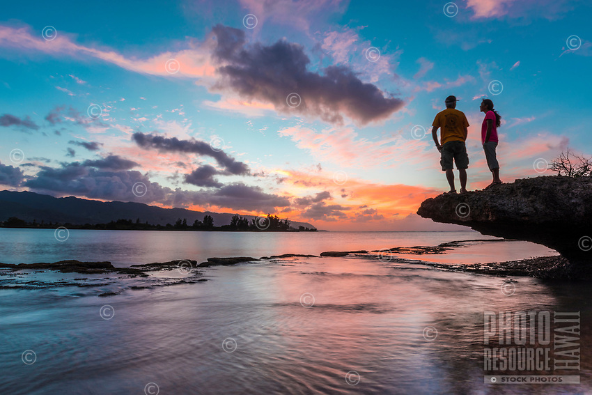 A couple enjoys the last of the day's sunset and surroundings on the North Shore of O'ahu.