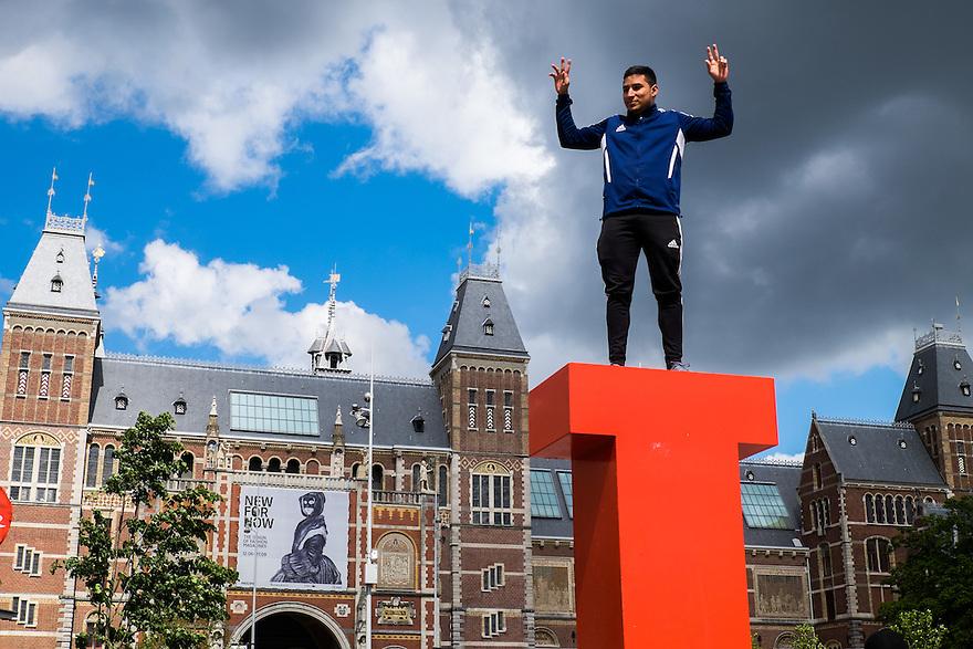 Nederland, Amsterdam, 30 mei 2015<br /> Toerist poseert voor de foto die zijn vrienden maken op de I van het  I amsterdamlogo en het Rijksmuseum.   <br /> Foto: Michiel Wijnbergh