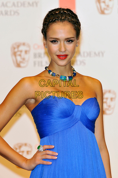 JESSICA ALBA .At the 2011 Orange British Academy Film Awards (BAFTAs), Royal Opera House, Covent Garden, London, England, UK, February 13th 2011..press room half length strapless blue dress hand on hip ring green stone necklace red lipstick hair up plaits braids .CAP/PL.©Phil Loftus/Capital Pictures.