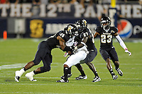 25 October 2011:  FIU linebacker Jordan Hunt (25) and defensive back Jose Cheeseborough (27) combine to tackle Troy wide receiver Jaquon Robinson (83) in the third quarter as the FIU Golden Panthers defeated the Troy University Trojans, 23-20 in overtime, at FIU Stadium in Miami, Florida.