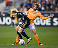 Brian Carroll (7) of the Philadelphia Union fights for the ball with Brad Davis (11) of the Houston Dynamo during the game at PPL Park in Chester, PA.  Houston defeated Philadelphia, 2-1, to take home the one goal advantage in the home and home series..