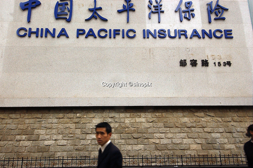 People pass an advert for China Pacific Insurance in Chongqing, Western China. China Pacific Insurance Co., is the mainland's second-biggest insurance firm..12-APR-05
