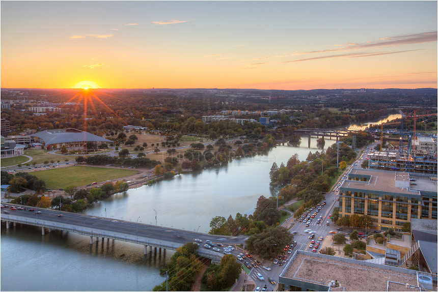Taken from the roof of a building at the corner of Congress and Casar Chavez, this photograph shows Lady Bird Lake as it flows into Austin from the west. In the foreground is the First Street Bridge and the green fields of Zilker Park.