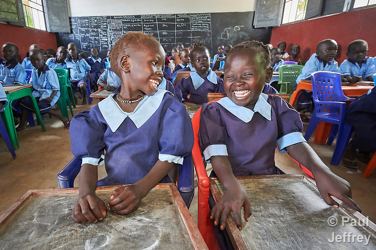 Girls laugh as they hold chalkboard tablets in a primary school in Bunj, South Sudan, sponsored by Jesuit Relief Service. The community is host to more than 130,000 refugees from the Blue Nile region of Sudan, and JRS provides educational and psycho-social services to both refugees and the host community.