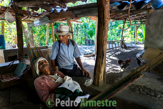 November 10, 2014. &quot;Water it&acute;s the real thing&quot;<br /> Ernesto Montes with his neighbour, Santos Rodriguez, in his house in Nejapa (El Salvador). He has the illnes of Chikungunya and he doesn&rsquo; t have drinking water at home. The people of Nejapa in El Salvador, have no drinking water because the Coca -Cola company overexploited the aquifer in the area, the most important source of water in this Central American country. This means that the population has to walk for hours to get water from wells and rivers. The problem is that these rivers and wells are contaminated by discharges that makes Coca- Cola and other factories that are installed in the area. The problem can increase: Coca Cola company has expansion plans, something that communities and NGOs want to stop. To make a liter of Coca Cola are needed 2,4 liters of water. &copy;Calamar2/ Pedro ARMESTRE