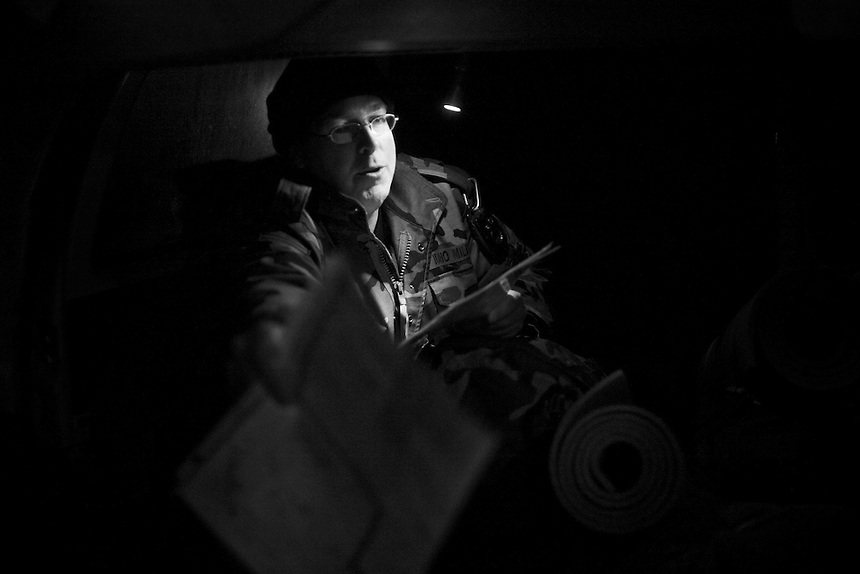 Captain Willard Protsman of the Idaho Light Foot Militia reaches for a route map at the start of an overnight training session in the mountains along the Idaho and Montana border.