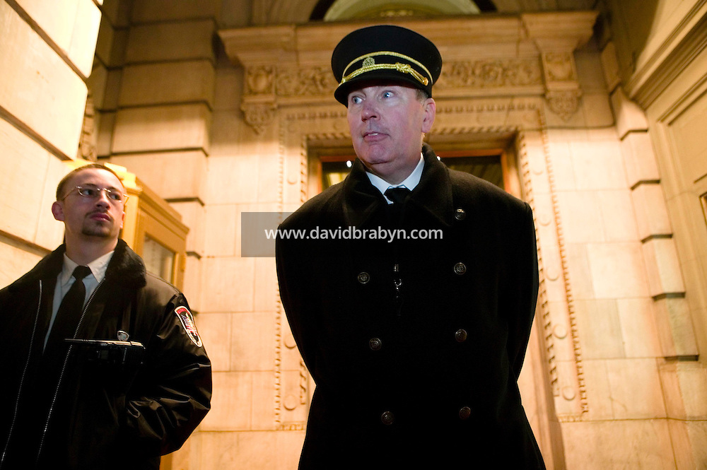 11 January 2006 - New York City, NY - Plaza hotel doorman Ed Trinka (R) awaits visitors in the entrance to the landmark hotel which is currently under renovation, 11 January 2006, New York City, USA. Trinka has been doorman at the Plaza since 1963.