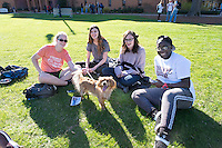 Friends Emily Sullivan, Amber Travis, Alyssa Moncrief, and Deborah Eseyin hang out on the Drill Field with Argus the dog.<br />  (photo by Megan Bean / &copy; Mississippi State University)
