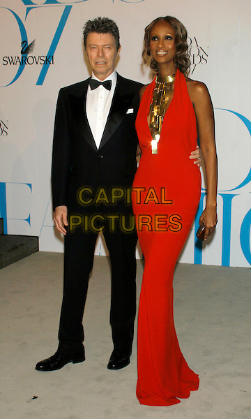 DAVID BOWIE & IMAN.2007 CFDA Fashion Awards at the New York Public Library, New York, NY, USA..June 4th, 2007.full length black tuxedo red dress gold necklace halterneck plunging married husband wife .CAP/LNC/RAO.©RAO/LNC/Capital Pictures