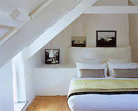 Three small paintings of exteriors of traditional Welsh cottages are the only adornment on the otherwise all-white lime-washed bedroom walls