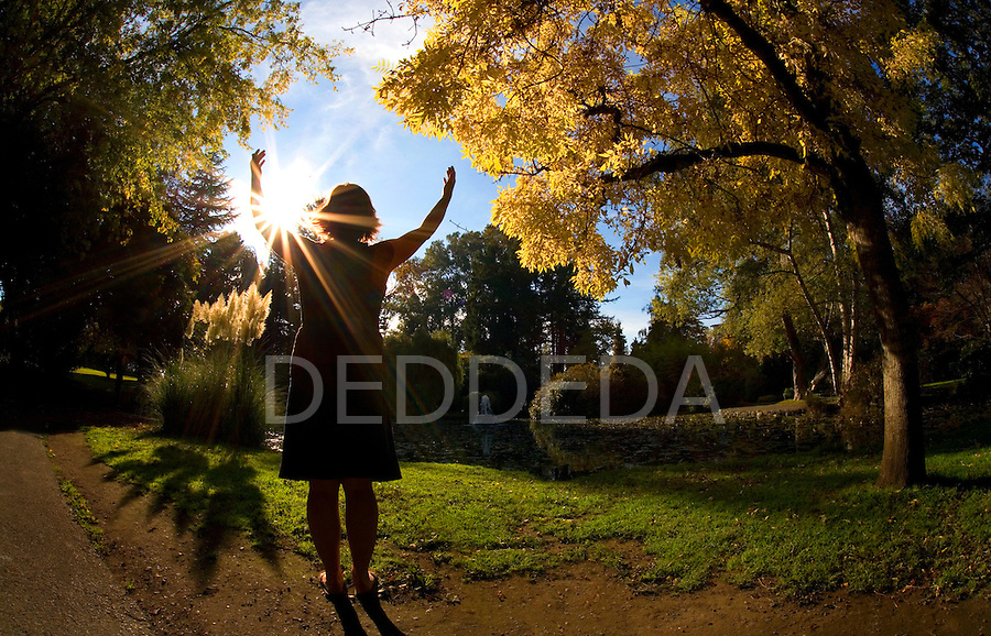 A woman prays in a park with sunlight streaming through during autumn.