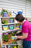 63821-203.05 Woman at potting bench with containers and flowers in spring, Marion Co. IL