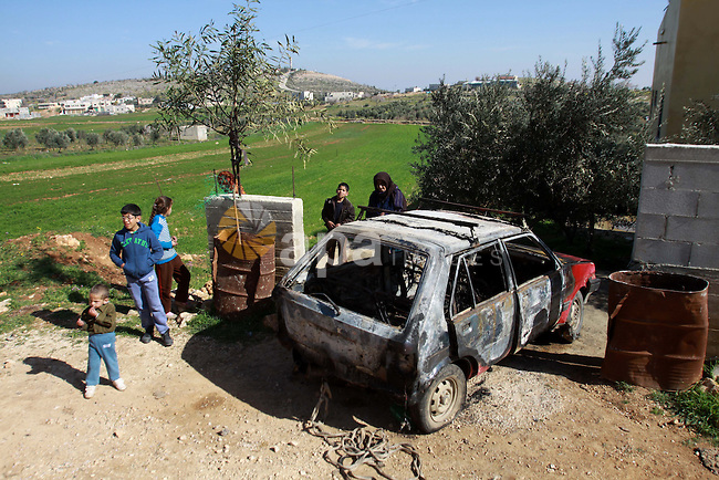 Palestinian children inspect a burnt car in the West Bank village of Qusra near Nablus on February 21, 2013. Israeli settlers torched seven cars in the northern West bank village of Qusra, Palestinian security sources said. Photo by Nedal Eshtayah